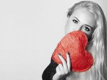 Schöne blonde Frau mit rotem Herzen Stockfoto