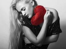 Schöne blonde Frau mit rotem Herzen Stockbild