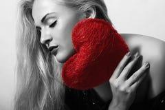 Schöne blonde Frau mit rotem Herzen Stockfotografie