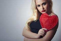 Schöne blonde Frau mit rotem Herzen. Schönheits-Mädchen. Zeigen Sie Liebes-Symbol. Das Day.Passion des Valentinsgrußes Stockbilder