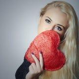 Schöne blonde Frau mit rotem Herzen. Schönheits-Mädchen. Zeigen Sie Liebes-Symbol. Valentinsgruß-Tag Stockfotos