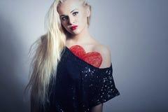 Schöne blonde Frau mit rotem Herzen. Schönheits-Mädchen. Zeigen Sie Liebes-Symbol. Valentinsgruß-Tag Stockfoto