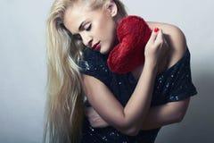 Schöne blonde Frau mit rotem Herzen. Schönheits-Mädchen. Zeigen Sie Liebes-Symbol. Valentinsgruß-Tag Stockfotografie