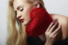 Schöne blonde Frau mit rotem Herzen. Schönheits-Mädchen. Zeigen Sie Liebes-Symbol. Valentinsgruß-Tag Lizenzfreies Stockbild