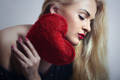 Schöne blonde Frau mit rotem Herzen. Schönheits-Mädchen. Zeigen Sie Liebes-Symbol. Valentinsgruß-Tag Lizenzfreie Stockbilder