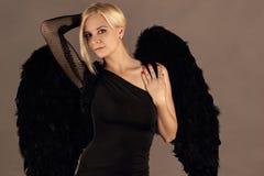 Schöne blonde Frau mit schwarzen Engelsflügeln Stockbild