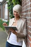 Schöne blonde Frau mit Tablette Stockbilder