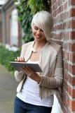 Schöne blonde Frau mit Tablette Stockfotografie