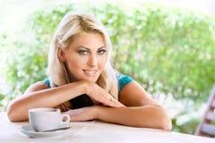 Schöne blonde Frau mit Tasse Kaffee im Sommercafé Stockbild