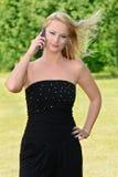 Schöne blonde Frau mit Telefon im Park Stockfotos