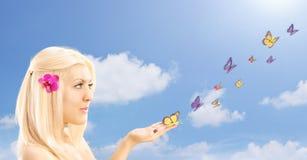 Schöne blonde Frau mit vielen Schmetterlingen auf ihrer Hand, agains Lizenzfreie Stockfotos
