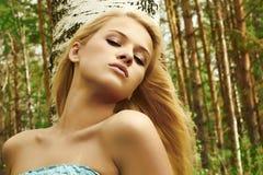Schöne blonde Frau nahe einem Baum in einem Wald Stockbilder