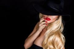 Schöne blonde Frau, sexy Modell mit den roten Lippen, gekleidet im schwarzen Wäscheausstattungs-Körperbadeanzug und im schwarzen  Stockfotografie