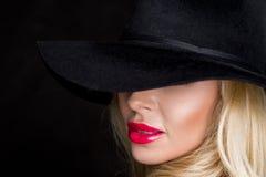 Schöne blonde Frau, sexy Modell mit den roten Lippen, gekleidet im schwarzen Wäscheausstattungs-Körperbadeanzug und im schwarzen  Lizenzfreie Stockfotografie