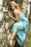 Schöne blonde Frau sitzt auf einem Baum in einem Wald Lizenzfreie Stockbilder