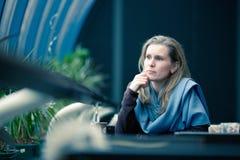 Schöne blonde Frau sitzt im Kaffee Lizenzfreie Stockbilder
