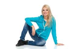 Schöne blonde Frau sitzt sich entspannte auf einem Boden, lächelt und betrachtet Kamera Stockbild