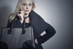 Schöne blonde Frau in Topcoat.Girl mit Handtasche Stockfotos