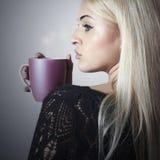 Schöne blonde Frau trinkender Kaffee. Cup.tea. Heißes Getränk Lizenzfreies Stockfoto