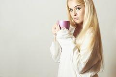Schöne blonde Frau trinkender Kaffee. Tasse Tee. Heißes Getränk Lizenzfreie Stockbilder
