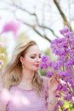 Schöne blonde Frau unter den blühenden Niederlassungen des Frühlinges Lizenzfreie Stockfotos