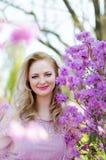 Schöne blonde Frau unter den blühenden Niederlassungen des Frühlinges Lizenzfreies Stockfoto
