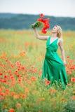 Schöne blonde Frau unter der blühenden Wiese mit rotem poppie Stockfotografie