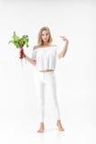 Schöne blonde Frau zeigt auf Rote-Bete-Wurzeln mit grünen Blättern auf weißem Hintergrund Gesundheit und Vitamine Lizenzfreies Stockfoto