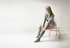 Schöne blonde Frau zieht ihre grauen Socken hoch Stockfotos