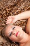 Schöne blonde Frauen-Haltungen auf Leopard-Decke. Stockfotografie
