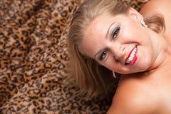 Schöne blonde Frauen-Haltungen auf Leopard-Decke. Lizenzfreies Stockfoto