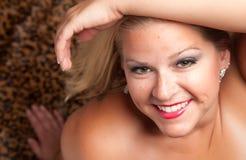Schöne blonde Frauen-Haltungen auf Leopard-Decke. Stockfotos