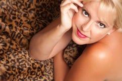 Schöne blonde Frauen-Haltungen auf Leopard-Decke. Stockbild