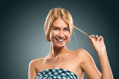 Schöne blonde Frauenhand des Porträts, die eine Haarsträhne hält Stockfotografie