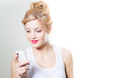 Schöne blonde Frauenlesemitteilung auf Mobile Stockbild