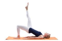 Schöne blonde Frauentrainingshinterteile und Hüftenmuskeln mit dem geraden Bein auf einer Matte Lizenzfreie Stockfotos