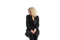 Schöne blonde gelockte Frau sitzt auf Stuhl im schwarzen Geschäft Sui Stockbild