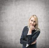 Schöne blonde Geschäftsfrau denkt an betriebswirtschaftliche Probleme Lizenzfreie Stockfotografie