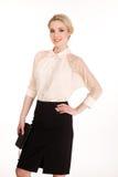 Schöne blonde Geschäftsfrau in der weißen Bluse und schwarzen im Rock lokalisiert auf Weiß Lizenzfreie Stockfotografie