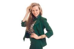 Schöne blonde Geschäftsfrau, die auf Kamera in der grünen Uniform lächelt Stockfotografie