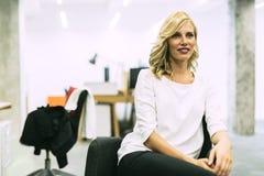 Schöne blonde Geschäftsfrau, die in einem Büro sitzt Lizenzfreie Stockfotografie
