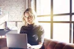 Schöne blonde Geschäftsfrau, die im sonnigen Büro arbeitet auf Laptop sitzt Konzept von Arbeitstragbaren geräten der jungen Leute Lizenzfreie Stockfotos