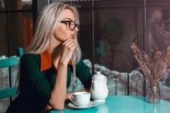Schöne blonde Geschäftsfrau im Café denkend an etwas Stockfoto