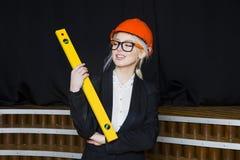 Schöne blonde Geschäftsfrau mit Anwendungsreihe im Dachbodenbüro im orange Bausturzhelm und -klage Lizenzfreies Stockfoto