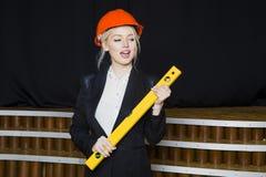 Schöne blonde Geschäftsfrau mit Anwendungsreihe im Dachbodenbüro im orange Bausturzhelm und -klage Lizenzfreie Stockfotos