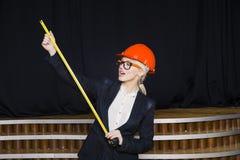 Schöne blonde Geschäftsfrau mit Anwendungsreihe im Dachbodenbüro im orange Bausturzhelm und -klage Stockbilder