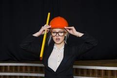 Schöne blonde Geschäftsfrau mit Anwendungsreihe im Dachbodenbüro im orange Bausturzhelm und -klage Stockbild