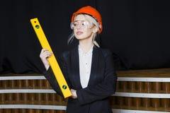 Schöne blonde Geschäftsfrau mit Anwendungsreihe im Dachbodenbüro im orange Bausturzhelm und -klage Lizenzfreies Stockbild