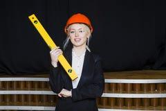 Schöne blonde Geschäftsfrau mit Anwendungsreihe im Dachbodenbüro im orange Bausturzhelm und -klage Lizenzfreie Stockbilder