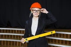 Schöne blonde Geschäftsfrau mit Anwendungsreihe im Dachbodenbüro im orange Bausturzhelm und -klage Stockfotografie